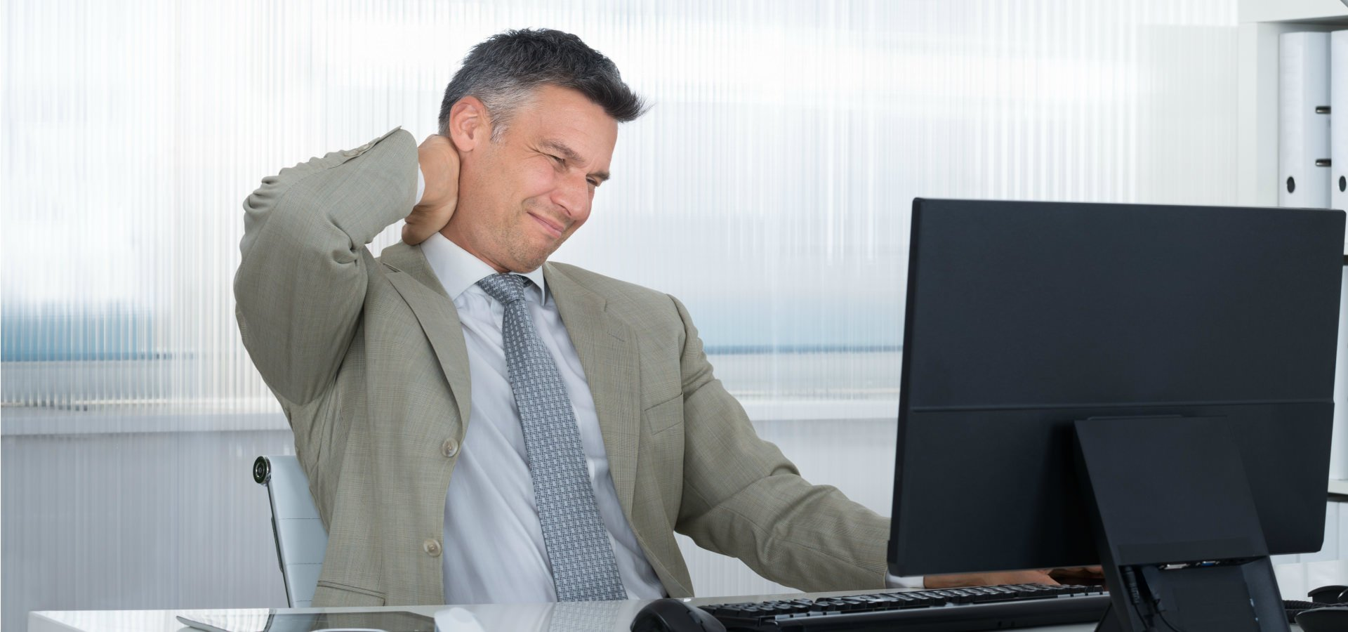 Man complaining of neck pain whilst sitting at a desk